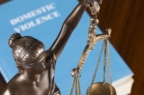 A mock law book on domestic violence next to Lady Justice.