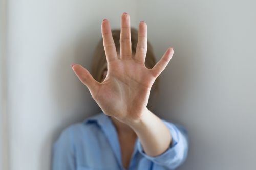 woman holding up her hand to block her face